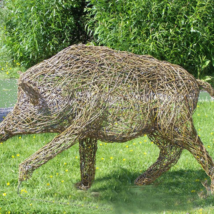 Side-on photo of walking wild boar sculpture