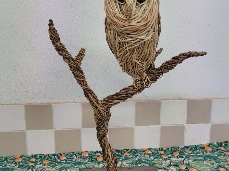 Barn owl sitting. Willow sculpture.