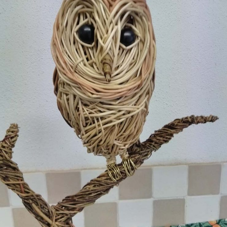 Barn owl sitting. Willow sculpture.