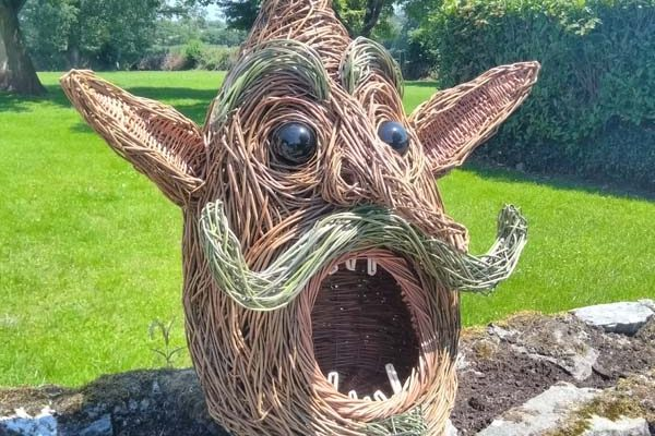 This double layered head is 3.5 foot high, is made of buff , brown and dyed willow and has large glass eyes.