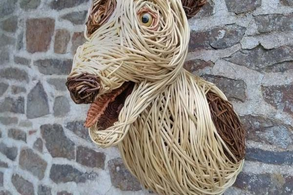 This dog is made of white willow and steamed willow with a buff willow tongue. It has fabric inside it's mouth and glass eyes.